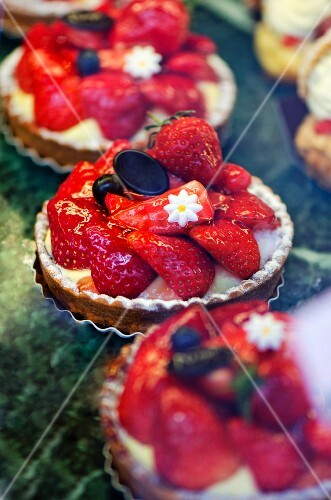 Strawberry tartlets on display in a bakery