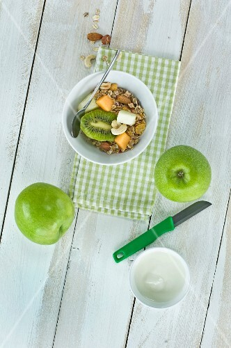A healthy breakfast: muesli with fresh fruits, nuts and milk, kiwi, apple and melon on a wooden table