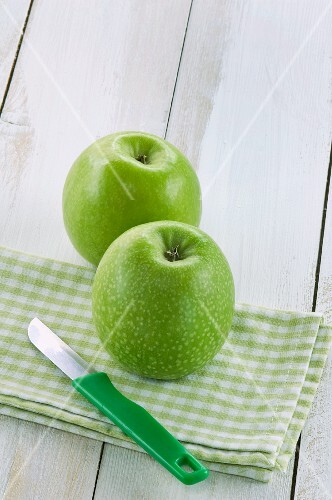 Two green apples on a napkin with a knife