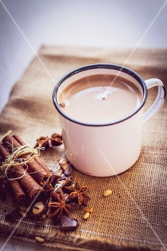 A mug of hot chocolate on a piece of jute with Christmas spices