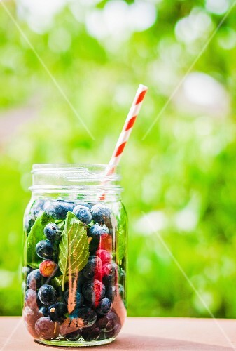 Iced tea with blueberries in a screw-top jar with a straw on a garden table