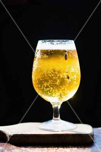 A glass of lager on a wooden board