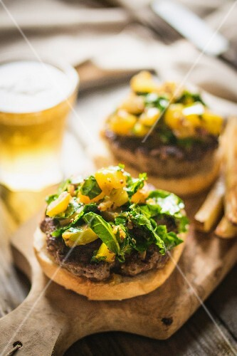 Grilled cheeseburgers with potatoes and beer on a chopping board