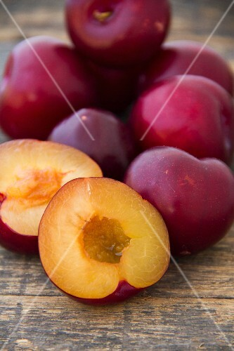 Fresh plums, whole and halved