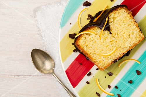 A slice of orange cake with chocolate glaze