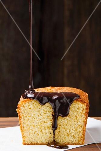 Chocolate glaze being poured over vanilla cake