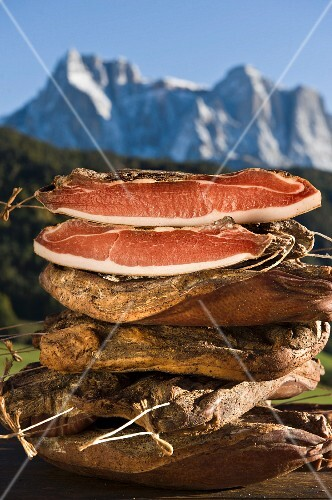 A pile of smoked bacon in front of Schlern mountain range, Kastelruth, Alto Adige, South Tyrol, Italy