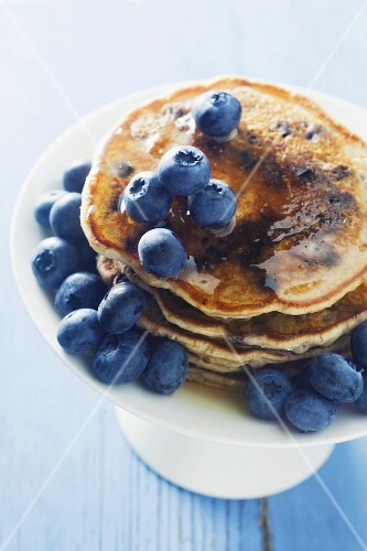 Pancakes with blueberries and honey on a cake stand