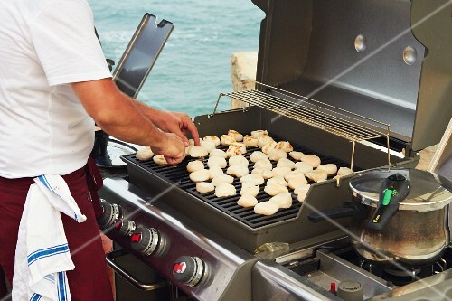 A cook grilling scallops at a wedding party by the sea