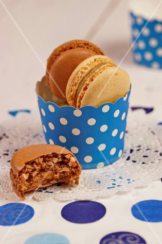 Chocolate and cappuccino macaroons in a blue-and-white paper cup