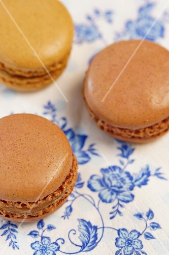 Chocolate and cappuccino macaroons on a blue-and-white floral paper cloth