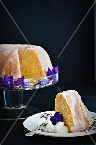 Lemon Bundt cake decorated with violets, sliced