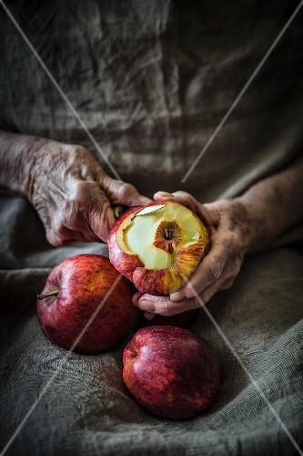 Old hands peeling red apples