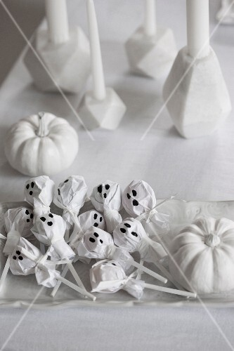 Lollies wrapped in white as little ghosts, white pumpkins and white candlesticks