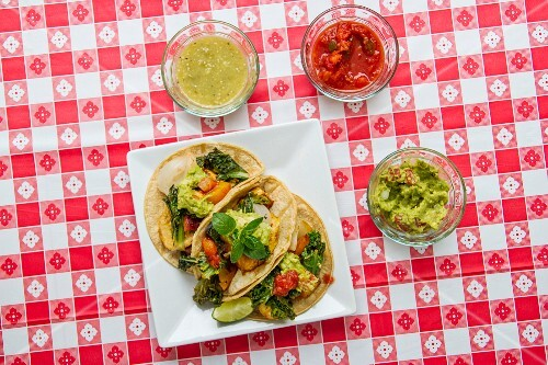 Vegan tacos with kale, guacamole, salsa, and salsa verde on a red-and-white checked tablecloth