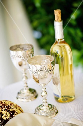 Two silver goblets and a bottle of wine for a Jewish wedding