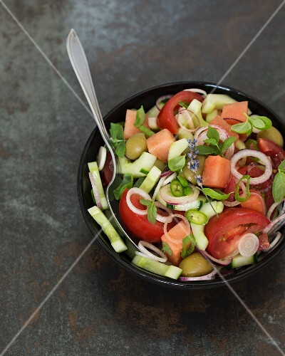 Fresh salad with tomatoes, cucumber, onions, olives, watermelon and herbs