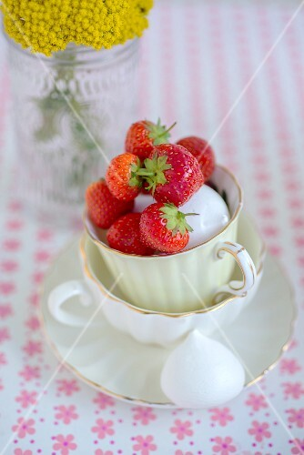 Strawberries and meringue bites in a stack of teacups on a floral-patterned surface