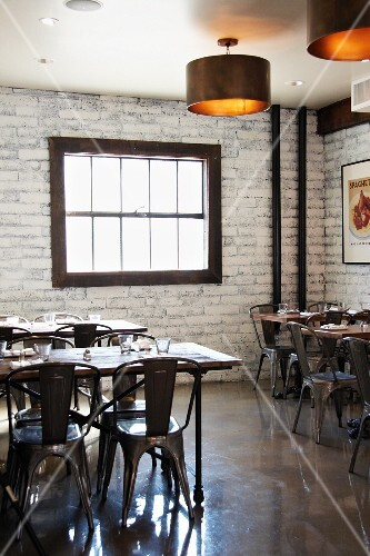 An industrial style Italian restaurant with wooden tables and metal chairs