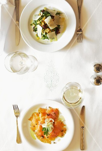 A festively laid table, seen from above, laid with rocket salad and salmon carpaccio