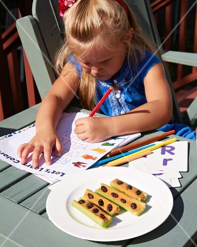 A little girl doing homework with a vegetable snack on a plate next to her