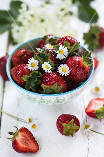 Fresh strawberries in a bowl with daisies