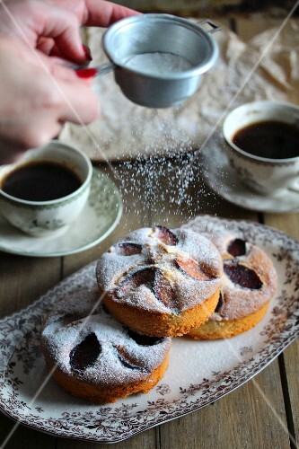 Hands sprinkling a plum and apple cake with icing sugar