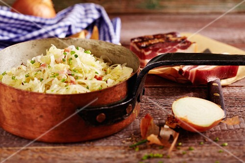 Bavarian coleslaw with onions and bacon in a copper pot