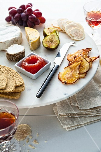 A cheese platter with quince jelly, grapes, figs and pears