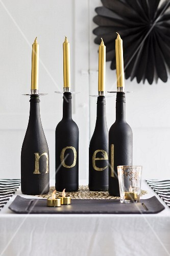 Four bottles used as candlesticks on Christmas table