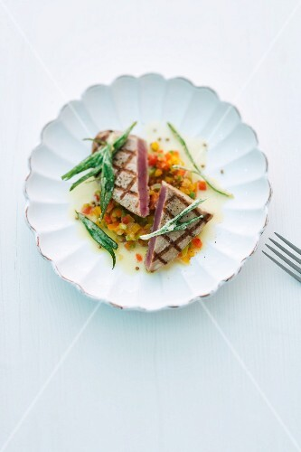 Grilled tuna fish fillet on a bed of vegetables