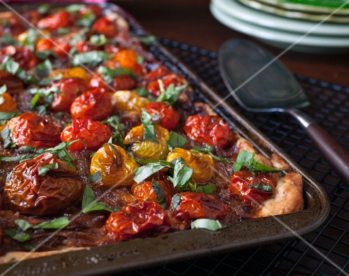 A puff pastry tart with red and yellow cherry tomatoes and basil