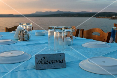 A table laid with a pastel-blue tablecloth with the Greek coast in the background