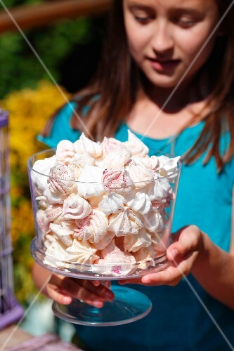 A girl holding a vase of meringues