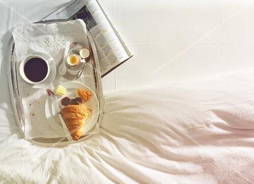 Breakfast in bed with coffee, egg and croissant