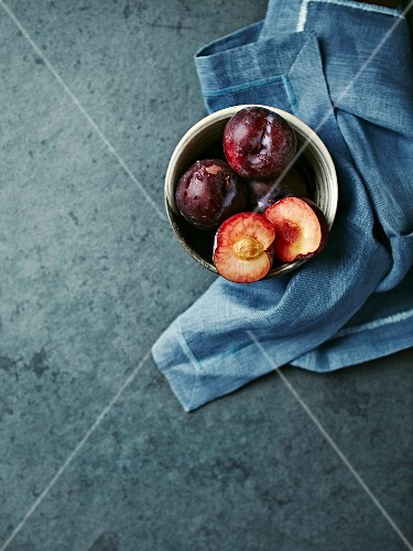 Red organic plums in a bowl