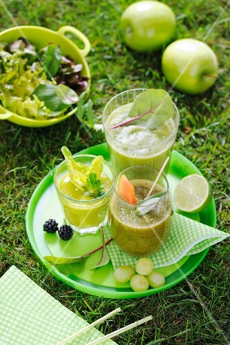 Three green smoothies on a tray in a garden
