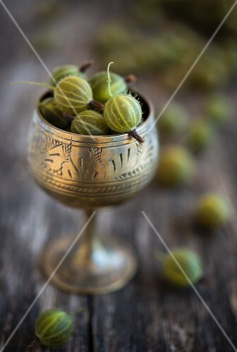 Green gooseberries in an antique silver goblet