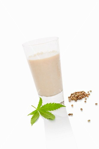 A glass of hemp milk on a white surface