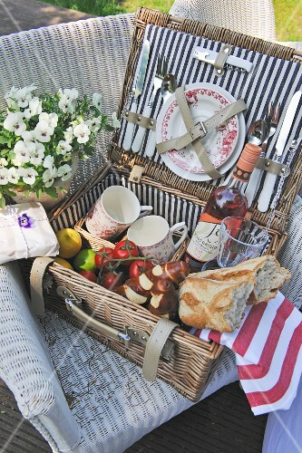An open picnic basket with crockery, wine, bread and tomatoes