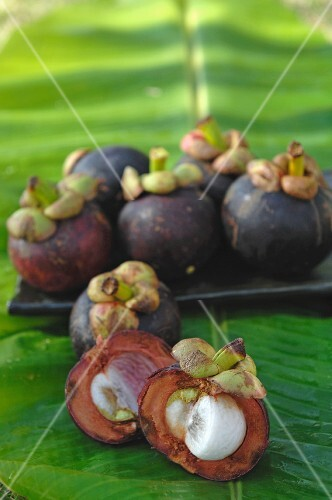 Mangosteens on a place and on a banana leaf