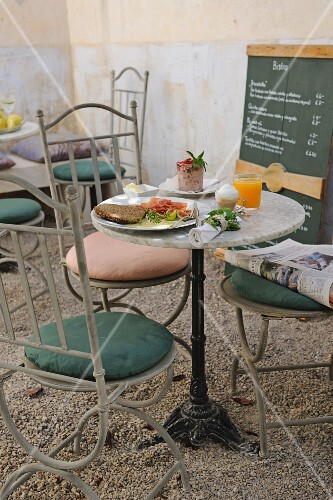 A bistro table with metal chairs next to a specials board in a courtyard
