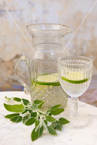 Water with slices of lime in a jug and a glass