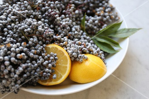 Elderberries with lemons in a white bowl on a marble surface