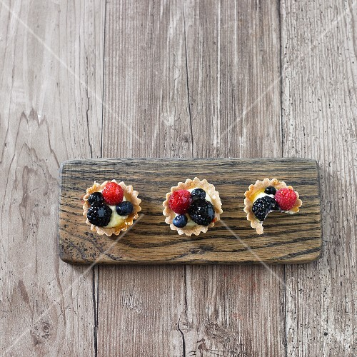 Organic mini fruit tarts on a wooden board (one with a bite taken out)