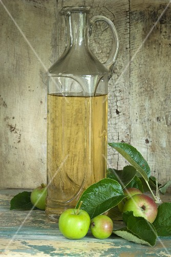A bottle of apple vinegar and apples in a rustic cupboard niche
