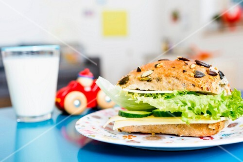 A cheese and salad sandwich on a pumpkin seed roll served with a glass of milk