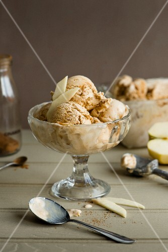 Apple, toffee and cinnamon ice cream in a glass bowl with apple wedges