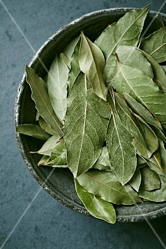 Dried bay leaves in a ceramic bowl