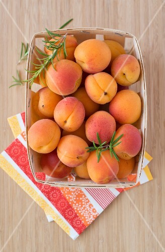 Fresh apricots in a wooden basket (seen from above)